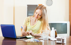 long-haired woman reading about medications on laptop in internet at home